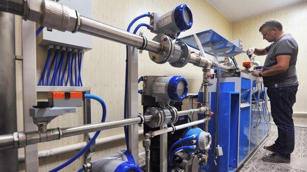 Инженер по метрологии устанавливает общедомовой счетчик воды для поверки