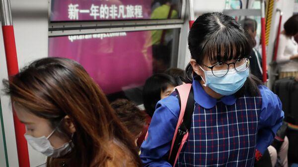 Жители Гонконга в защитных масках в вагоне поезда метро