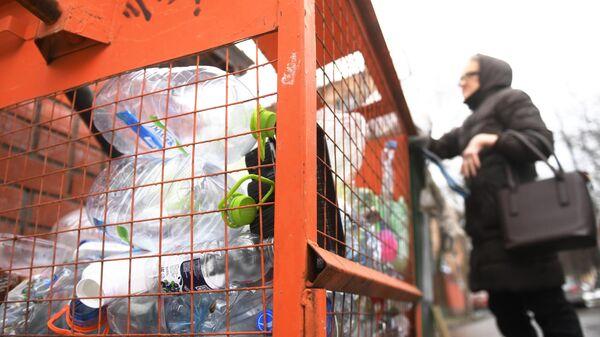 Женщина выкидывает мусор в контейнер для сбора отходов из пластика