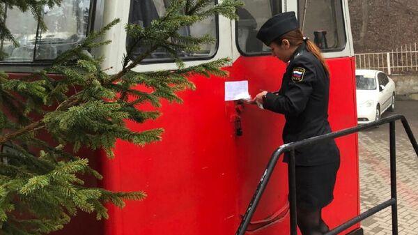 Сотрудница УФССП России по Краснодарскому краю опечатывает туристический поезд, возивший туристов по ущелью реки Курджипс