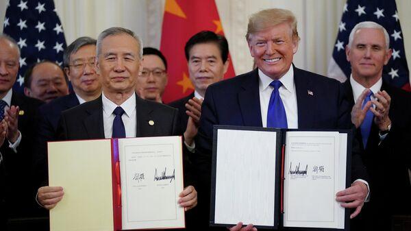 Вице-премьер Китая Лю Хэ и президент США Дональд Трамп после подписания первого пакета документов в рамках торгового соглашения в Вашингтоне. 15 января 2020