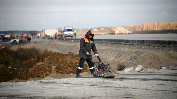 Рабочие на территории строительства взлетной полосы нового сегмента терминала аэропорта Домодедово