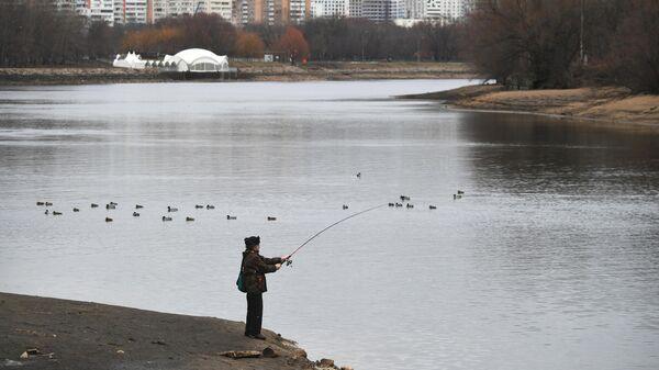 Мужчина ловит рыбу на территории Московского музея-заповедника Коломенское в Москве