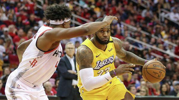 Игрок ХК Лос-Анджелес Лейкерс Леброн Джеймс (23) и игрок ХК Хьюстон Рокетс Дануэль Хаус в матче регулярного чемпионата НБА