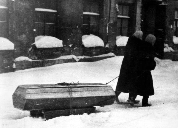 Жители города везут на санках гроб с умершем. Блокада Ленинграда