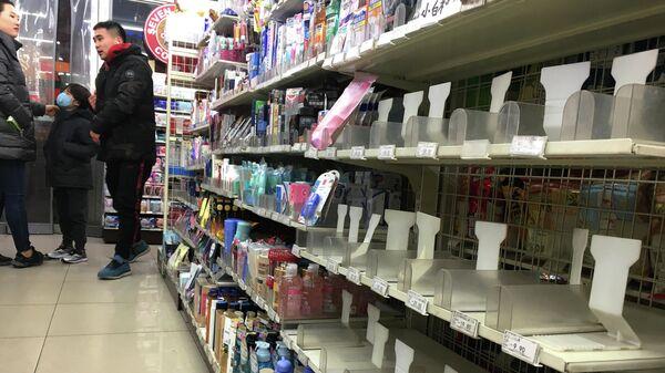 Пустая полка в магазине в Пекине, на которой были размещены защитные маски. 21 января 2020