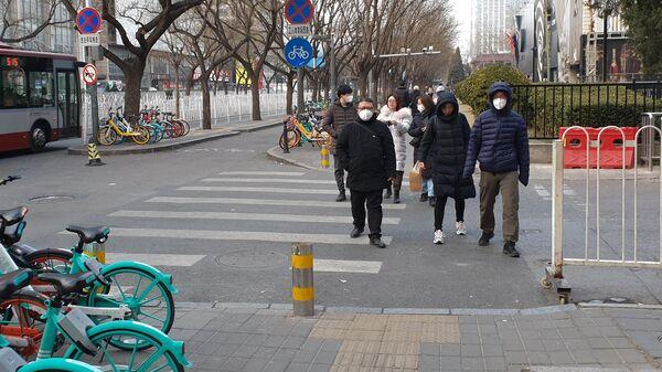 Люди в защитных масках на улице Пекина