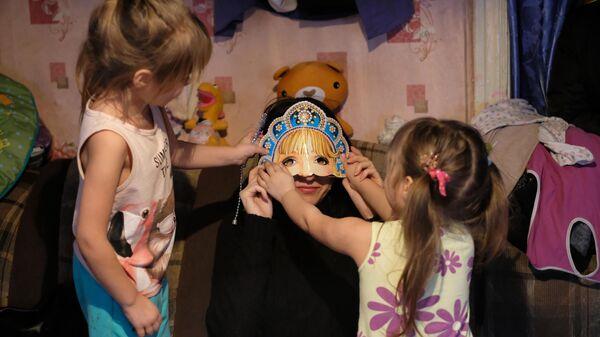 Сестры играют с волонтером Евгенией Горских, которая привезла семье подарки
