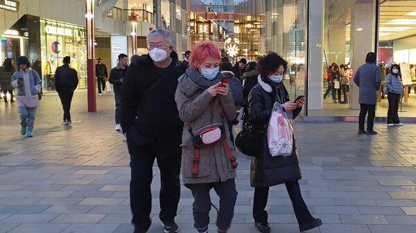 Прохожие в защитных масках на одной из улиц