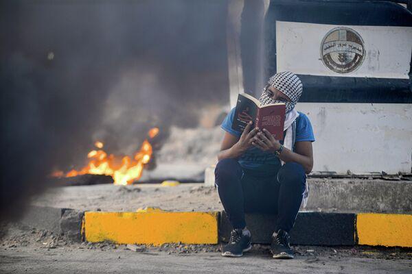 Антиправительственный демонстрант читает роман во время акции протеста в Эн-Наджафе