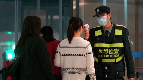 Сотрудник аэропорта проверяет пассажиров, покидающих международный аэропорт Ухань Тяньхэ в Ухане