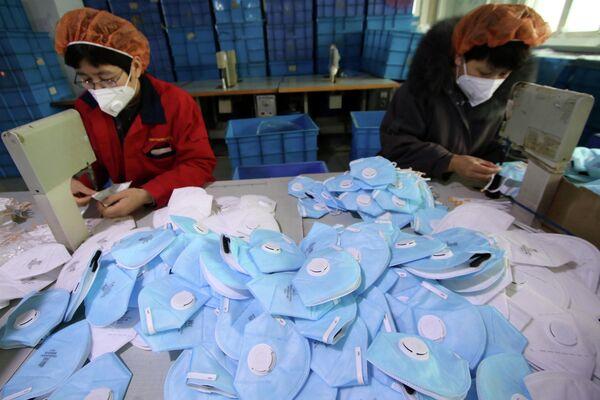 Производство защитных масок на фабрике в Ханьдане, провинция Хэбэй