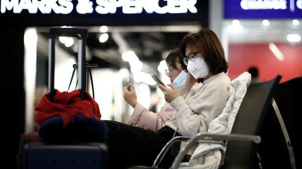 Туристы в защитных масках в аэропорту