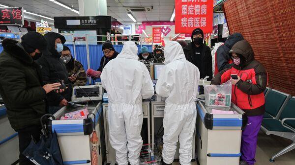 Работники аптеки в защитных костюмах в Ухане