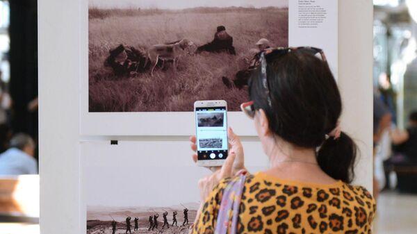 Посетительница фотографирует на мобильный телефон одну из фотографий на выставке работ победителей Международного конкурса фотожурналистики имени Андрея Стенина