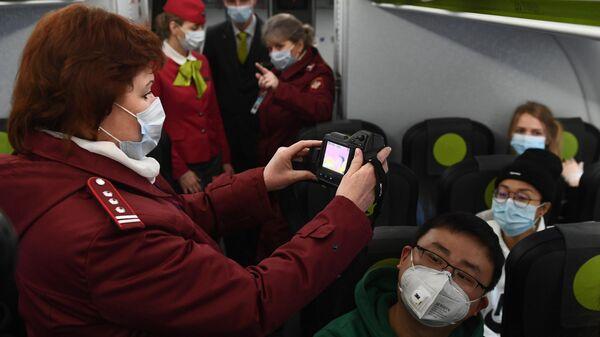 Сотрудники Роспотребназдора обследуют при помощи тепловизора пассажиров рейса авиакомпании S7, прибывшего из Пекина, в аэропорту Толмачево