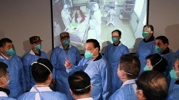Премьер-министр Китая Ли Кэцян разговаривает с медицинскими работниками в больнице города Ухань, проводят лечение от нового коронавируса