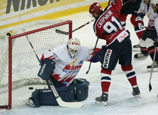 Армеец Олег Сапрыкин (N 91) забрасывает шайбу в ворота голкипера Металлурга Ильи Проскурякова в матче КХЛ