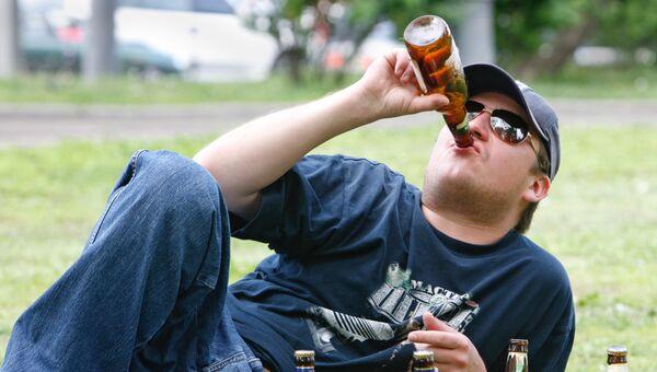 Молодой человек пьет пиво в парке. Архив
