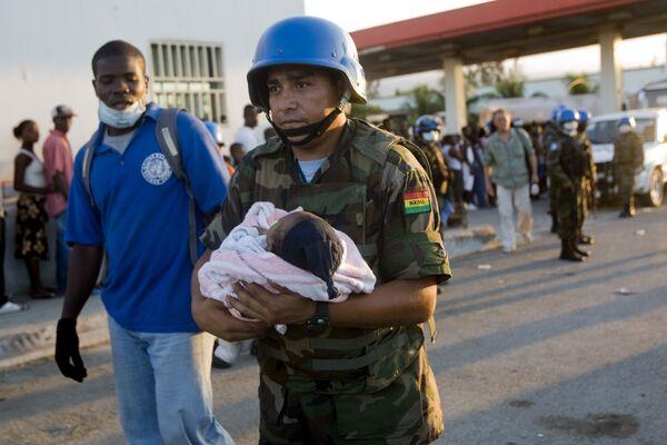 Миротворец ООН из Боливии несет гаитянского ребенка во время проведения гуманитарной операции помощи пострадавшим от землетрясения на Гаити.