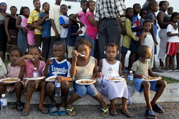 Дети едят пищу, розданную им в рамках гуманитарной операции на Гаити