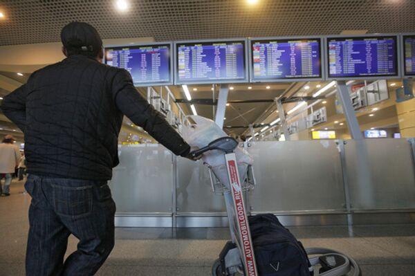 Пассажир у расписания вылета рейсов. Архив