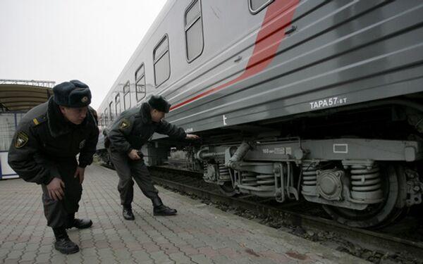 Наряд милиции осматривает вагоны поезда на железнодорожном вокзале. Архив