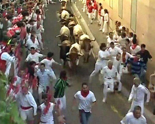 Разъяренные быки гонят сотни людей по улицам города