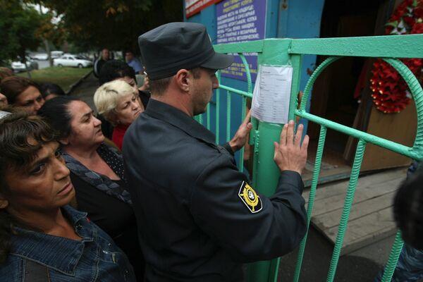 Родственники пострадавших от взрыва во Владикавказе у здания городского морга, где вывешены списки погибших в результате теракта