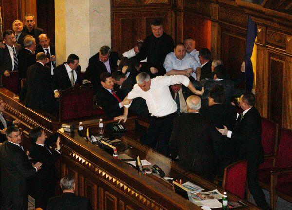 Представители Партии регионов и депутаты фракции БЮТ-Батькивщина дерутся в зале парламента Украины.