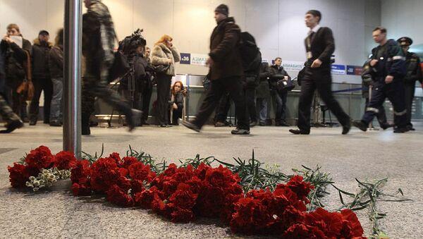 Люди несут живые цветы к месту трагедии в аэропорту Домодедово