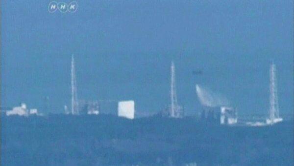 Вертолет сил внутренней безопасности Японии сбрасывает воду на аварийную японскую АЭС Фукусима-1, 17 марта 2011