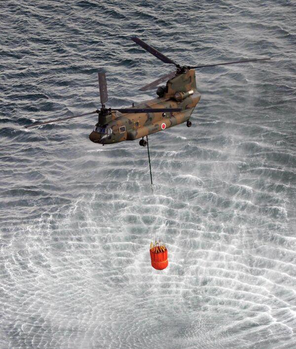 Вертолет набирает воду для устранения последствий аварии на АЭС Фукусима