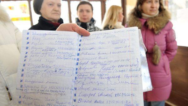 Родители демонстрируют списки детей-кандидатов на зачисление в первый класс одной из московских школ.