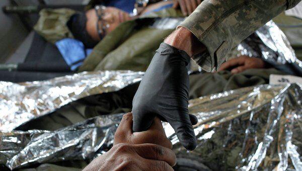 Врач проверяет состояние афганского ребенка, пострадавшего в ходе манифестаций в Кандагаре