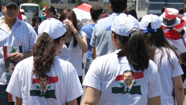 Девушки в Дамаске в футболках с изображением Башара Асада на фоне флага Сирии