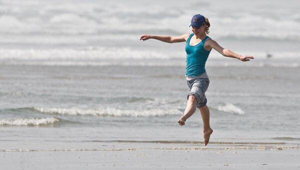 Девушка танцует на берегу. Архив