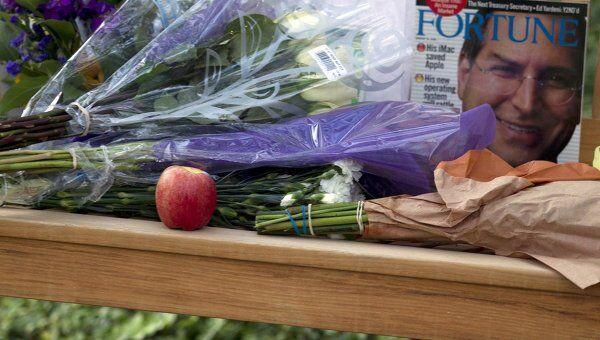 Люди несут цветы к штаб-квартире компании Apple в память о Стиве Джобсе