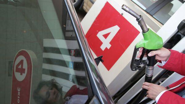Девушка заправляет машину бензином. Архивное фото