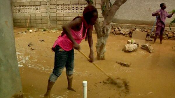 Жители Гаити вычерпывают воду и грязь после шторма Исаак