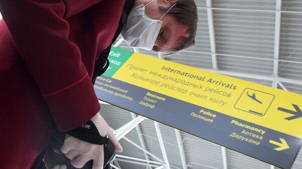 Сотрудник санитарно-карантинного пункта проводит дистанционную термометрию пассажиров, прибывших в международный аэропорт в Казани