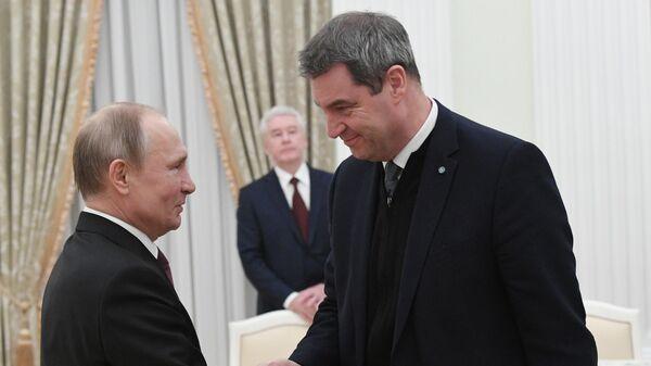Президент РФ Владимир Путин и премьер-министр федеральной земли Бавария Маркус Зедер во время встречи