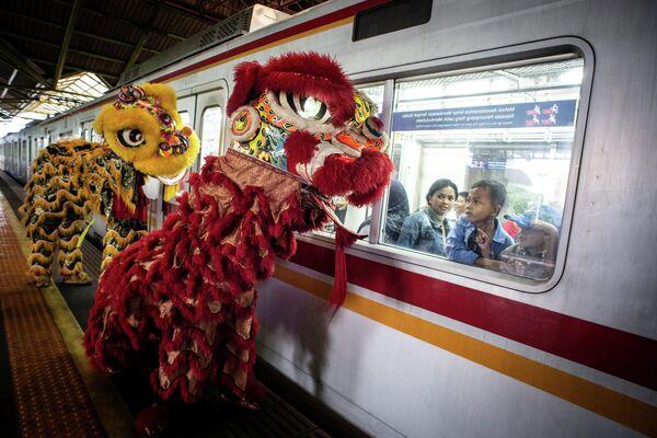 Пассажиры смотрят на выступление артистов, исполняющих Танец льва, на железнодорожной станции Гамбир во время празднования Нового года по лунному календарю в Джакарте
