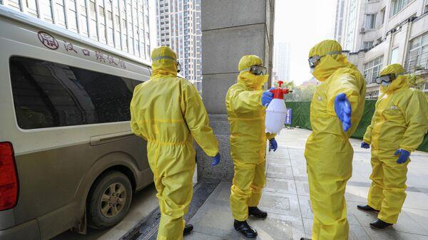 Сотрудники похоронного бюро в защитных костюмах проводят дезинфекцию в городе Ухань в провинции Хубэй