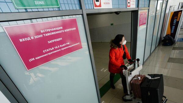 Туристка, прилетевшая из Китая, в аэропорту Владивостока