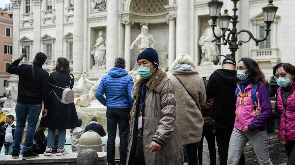 Туристы в респираторных масках возле фонтана Треви в центре Рима