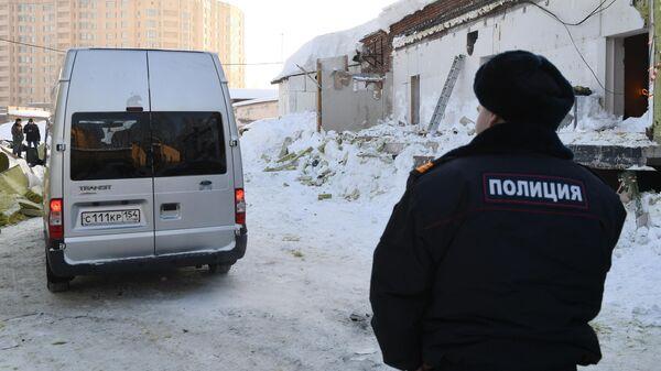 Автомобиль следственного комитета РФ и сотрудник полиции на месте обрушения кровли кафе в Новосибирске