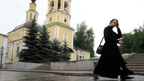 Священник идет мимо церкви