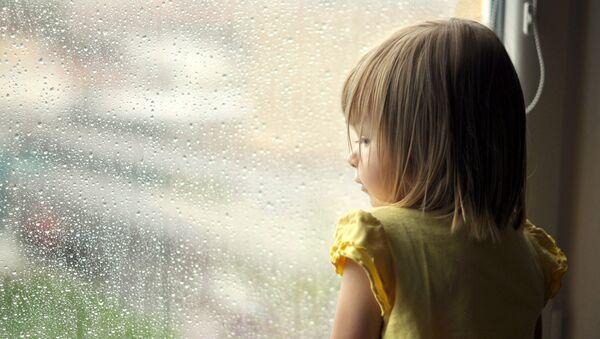 Девочка стоит у окна. Архивное фото