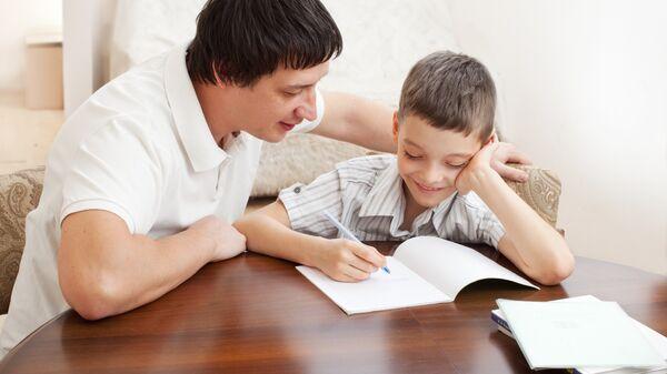 Папа помогает сыну делать домашнее задание